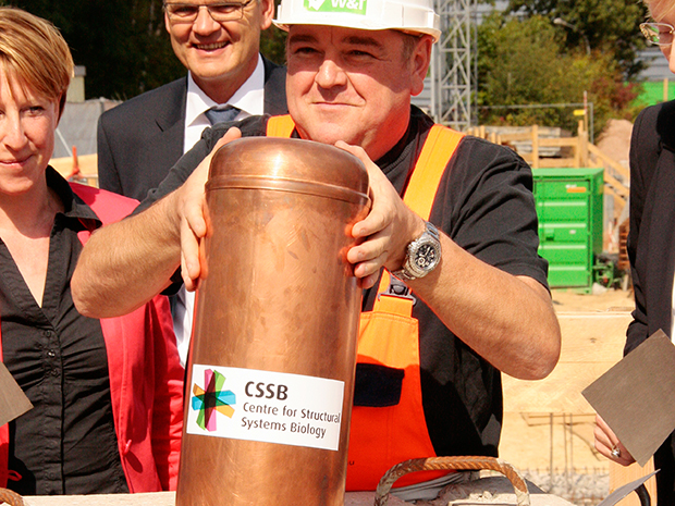 CSSB construction foreman Bernd Kretschmär adds the time capsule to  the foundation stone. PHOTO: Rosemary Wilson