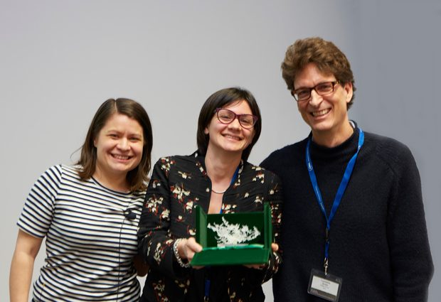 Rosa Paolicelli holds her trophy, a 3D printed microglia. Mariko Bennett and Cornelius Gross stand either side of her