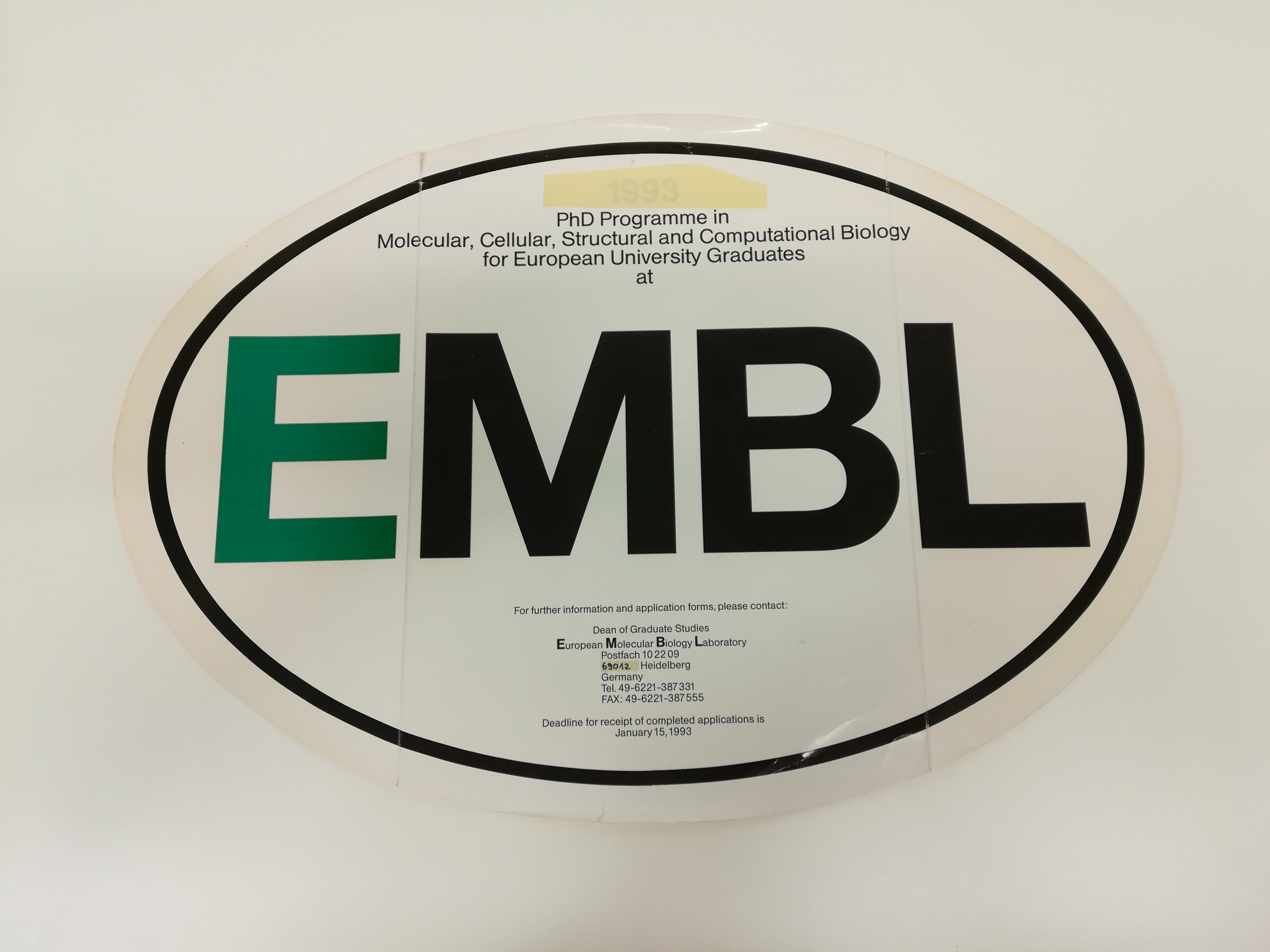 an oval sticker with the letters E M B L in the centre