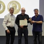 Chair of the Alumni Association Gareth Griffiths (left) and Director of EMBL-EBI Ewan Birney (right) present Nils Gehlenborg with the John Kendrew Award. PHOTO: Photolab /EMBL