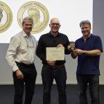 Chair of the Alumni Association Gareth Griffiths (left) and Director of EMBL-EBI Ewan Birney (right) present Nils Gehlenborg with the John Kendrew Award. PHOTO: Photolab /EMBL