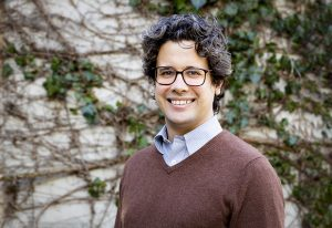 A smiling Santiago Rompani, new group leader at EMBL Rome, stands in front of a vine covered wall
