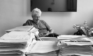 Black and white photo of Phil Avner sitting in his office and looking at his smartphone. a large stack of papers on his desk