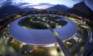Circular beamline building, surrounded by illuminated Grenoble city in the evening and the alps in the background.