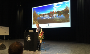 """Oliver Billker, Director of MIMS, is standing at the podium in front of a microphone. Behind him, a projected slide says """"Welcome to Umeå University""""."""