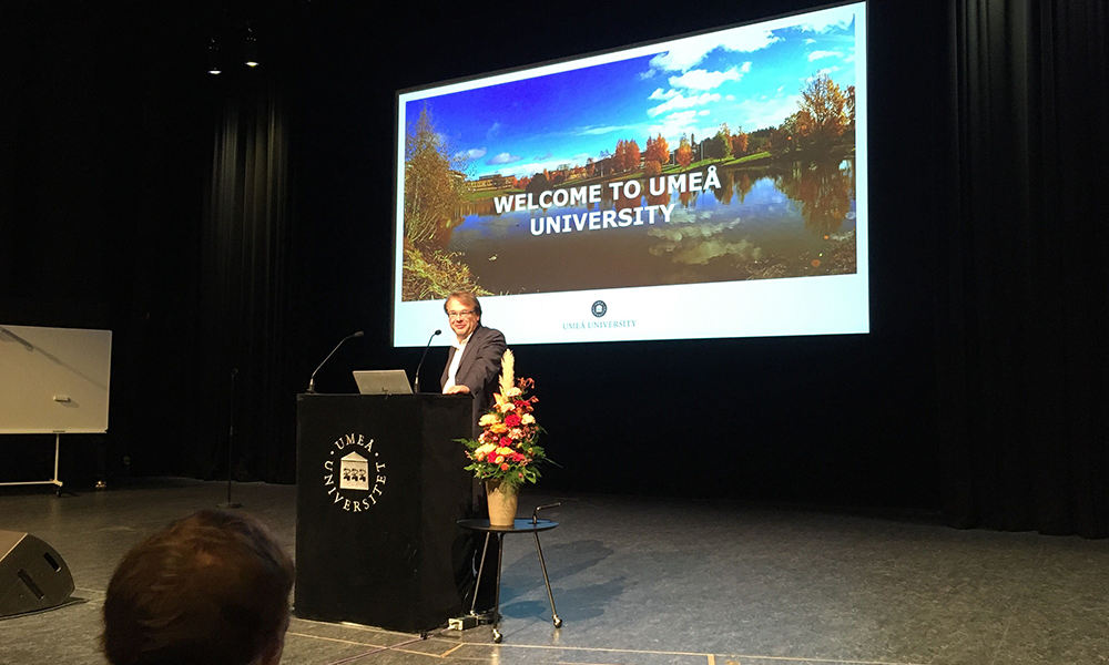 "Oliver Billker, Director of MIMS, is standing at the podium in front of a microphone. Behind him, a projected slide says ""Welcome to Umeå University""."