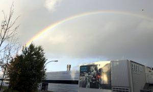 Rainbow on a cloudy sky above technical buildings.