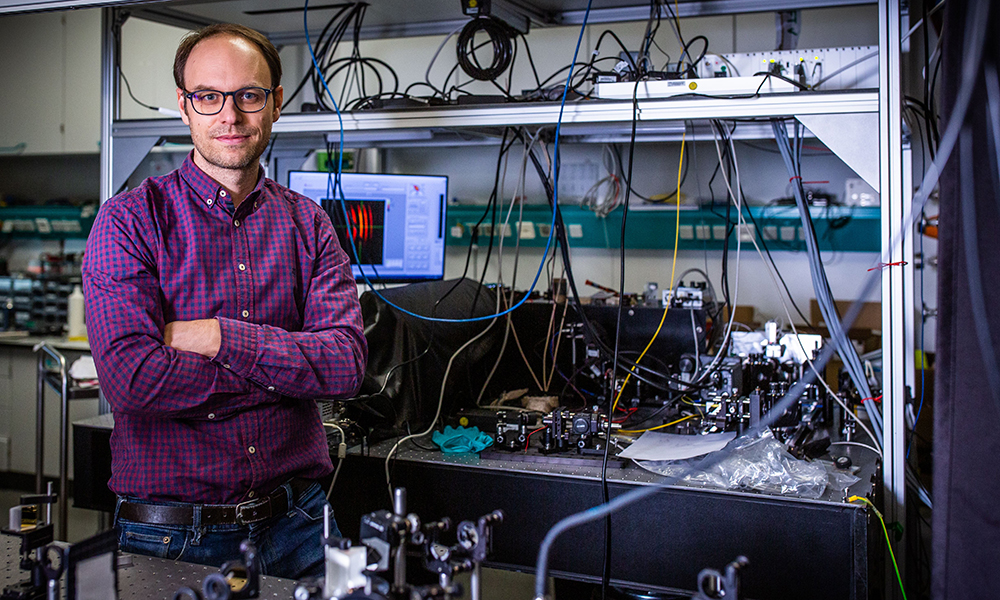 Male scientist stands in front of machinery in his lab.