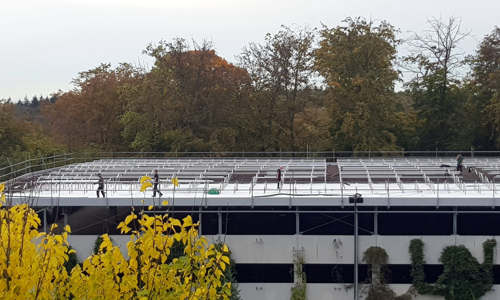 Car parking rooftop with a solar power plant under construction on it.