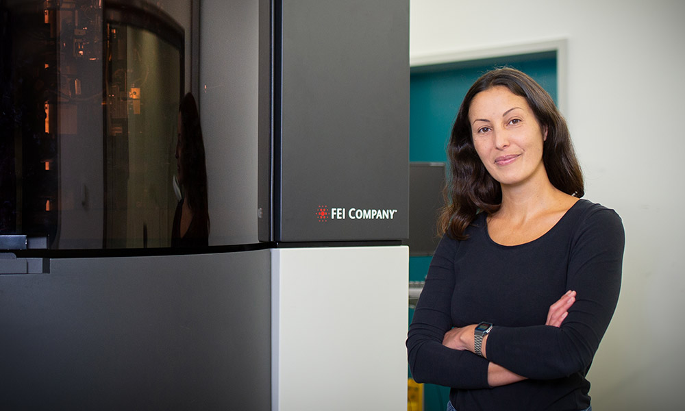 Female scientist stands in front of electron microscope that is taller than she is