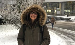 Woman with glasses wearing a parka stands in the snow outside a building at EMBL