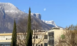 Snowy mountains behind functional buildings. The Moon is up in the sky.