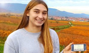 Maria-Theresa Licka holding a smartphone displaying an app she developed. Vineyards, houses and hills in the background.