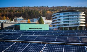 The newly installed solar array at EMBL's site in Heidelberg. In the foreground are rows of solar panels, with the ATC building shown behind.