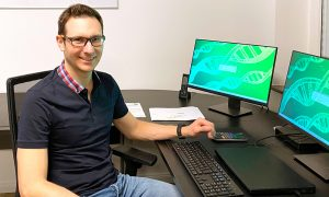 Man in black t-shirt and jeans wearing glasses sits in front of two computer screens.