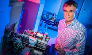 Older male scientist stands in front of machinery in a blue-lit room