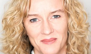 Head shot of female social scientist with blond curly hair and blue/grey eyes.