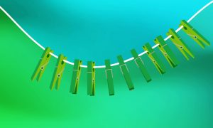 Several clothes pegs are attached to a washing line, which is bent into a curve.