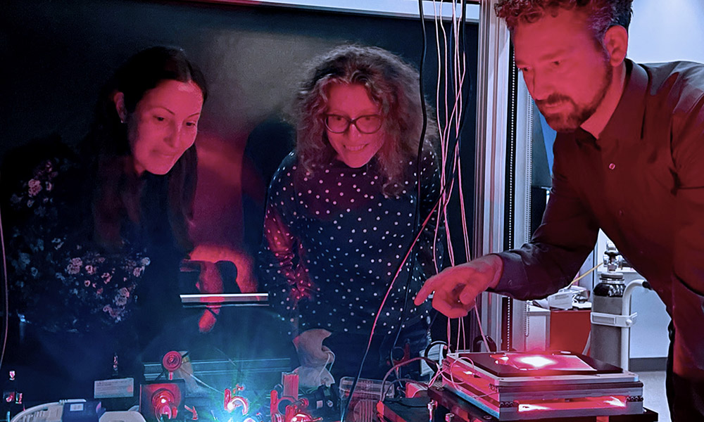 Three researchers surround microscopy equipment in a dark room with red lighting.