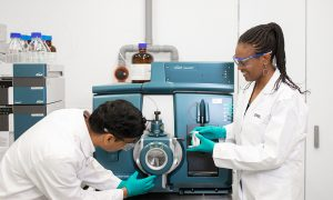 Two scientists in lab coats working on an instrument in the lab.
